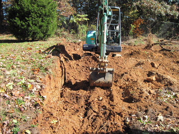 Excavating into hill for retaining wall