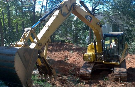 Excavator digging stump removal grinding